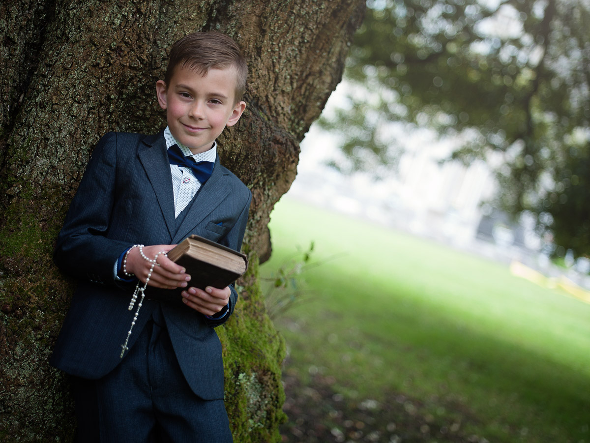 bay posing for communion photography under the tree holding a bible