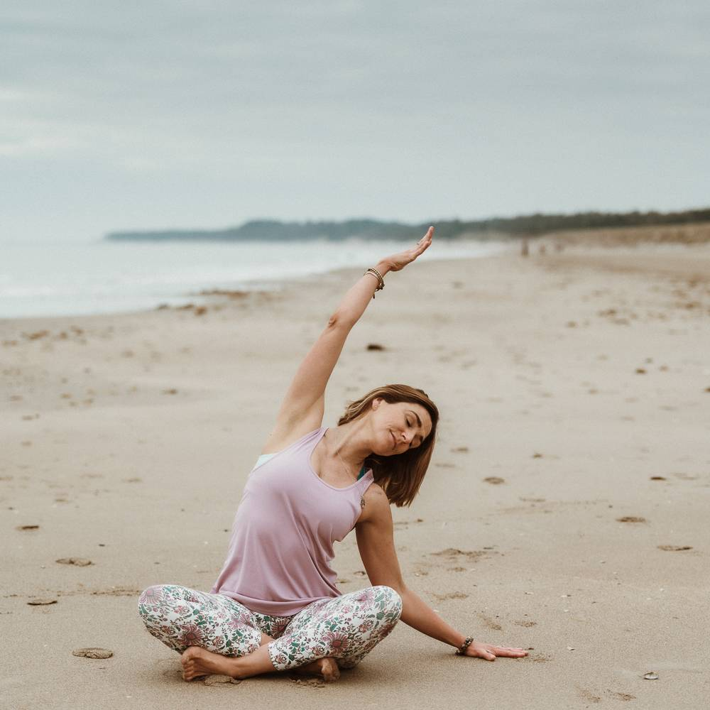 Yoga teacher performing a pose on the beach in Curracloe, wexford