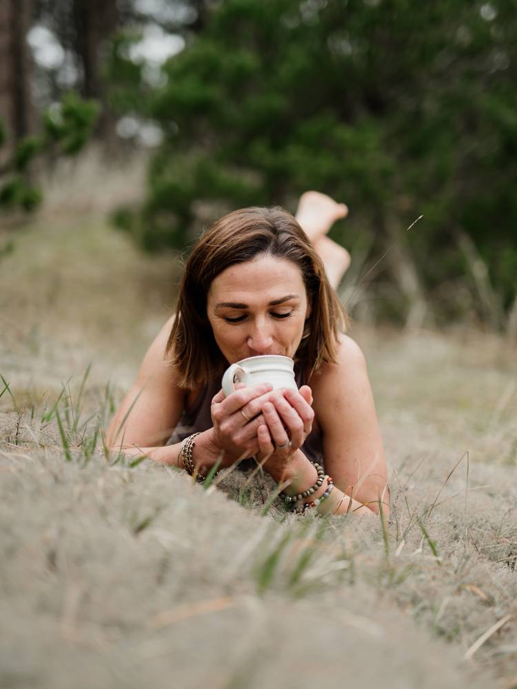 Yoga teacher drinking cacao on branding photo session in Curracloe forest