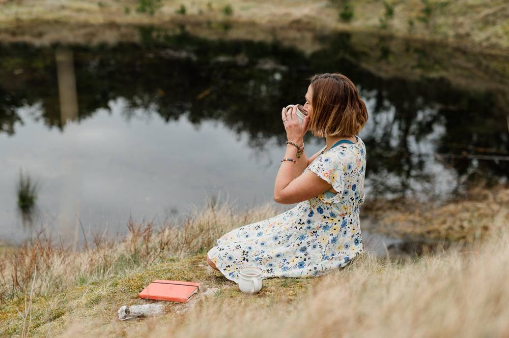 Yoga teacher with cup of cacao by the lake  on branding photo session in Wexford