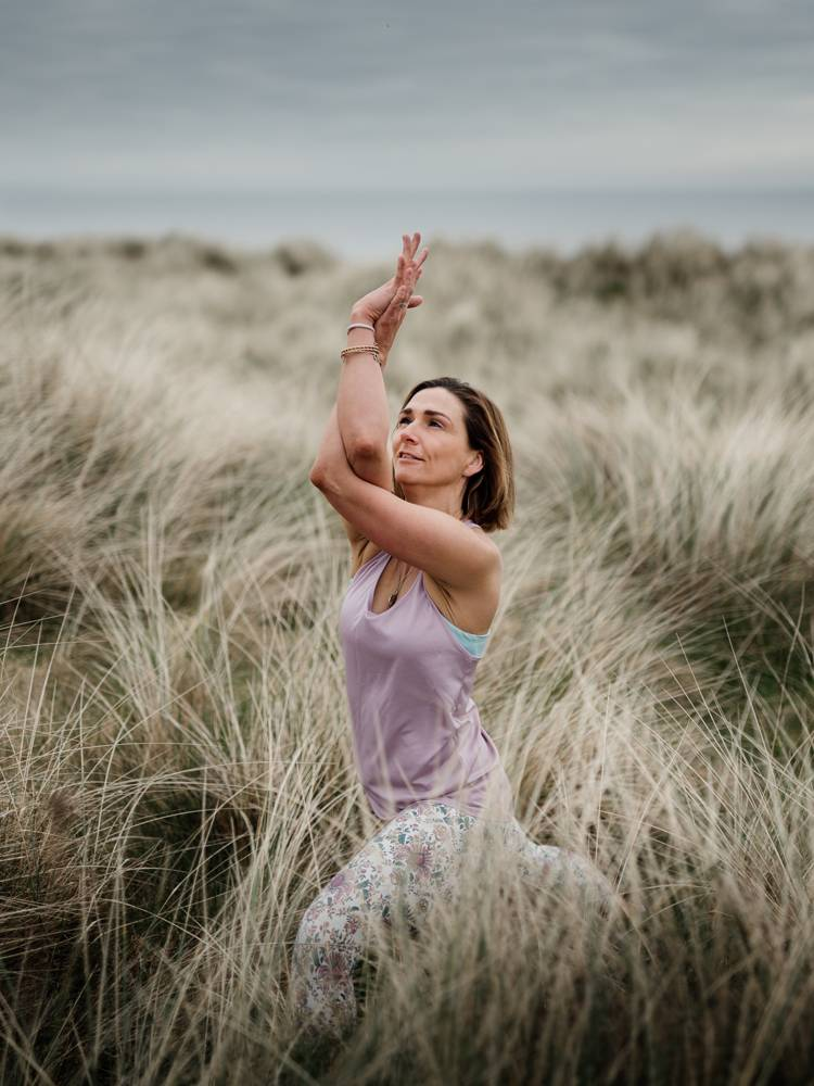 Yoga teacher posing in sand dunes on branding photo session in Wexford